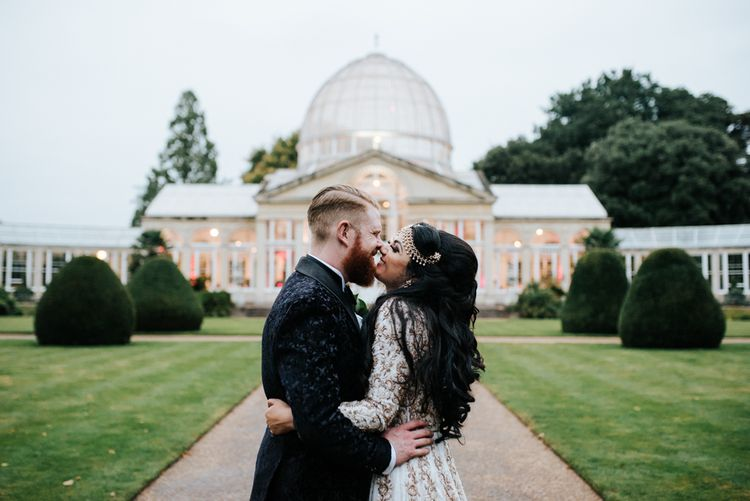 Bride and groom kissing in front of Syon Park wedding venue