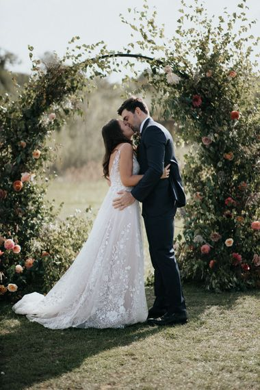 Bride and groom kissing in front of the ceremony floral moon gate at Willow Marsh Farm