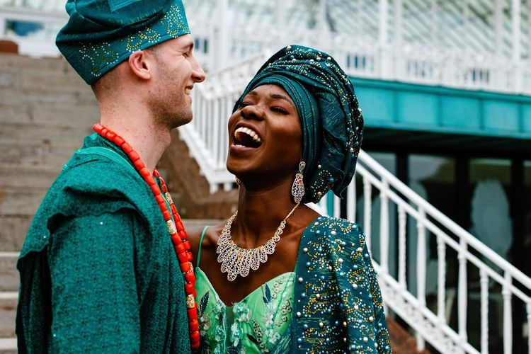 Bride and groom in green Nigerian outfits laughing together
