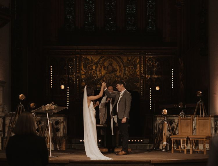 Bride and groom exchanging vows at their Holy Trinity Brompton Church wedding ceremony