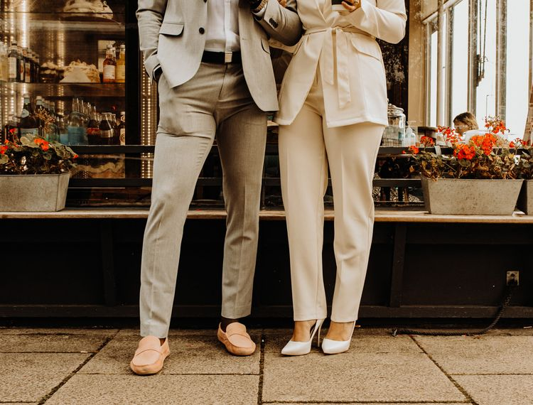 Groom in grey suit and pink loafers and bride in Ivory trouser suit and pumps