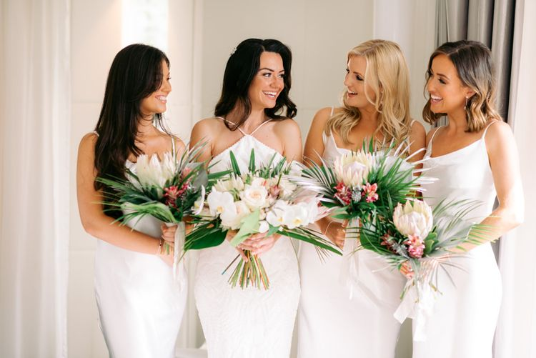 White bridal and bridesmaid dresses with bridal party holding King Protrea wedding flowers