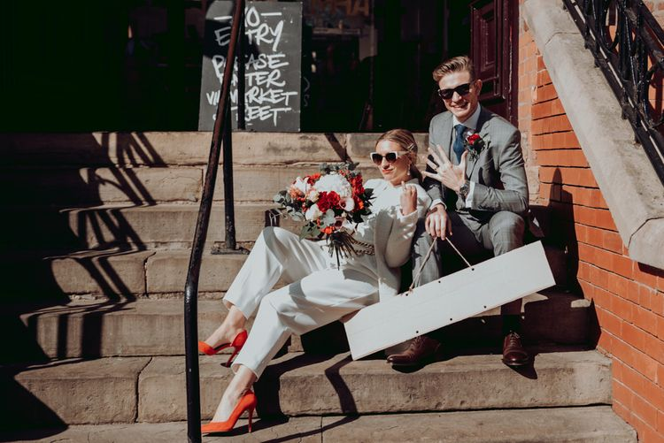时尚的新娘和新郎在他们的亲密微婚礼后炫耀他们的结婚戒指