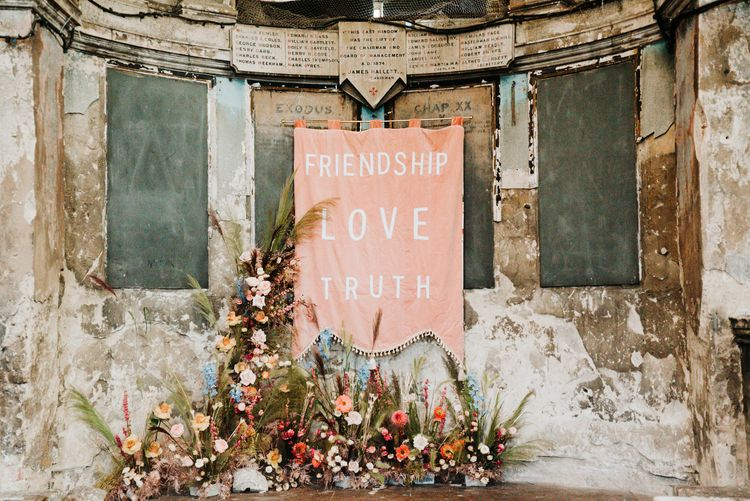 Pink fabric wedding sign and colourful flowers decorating the industrial wedding venue altar