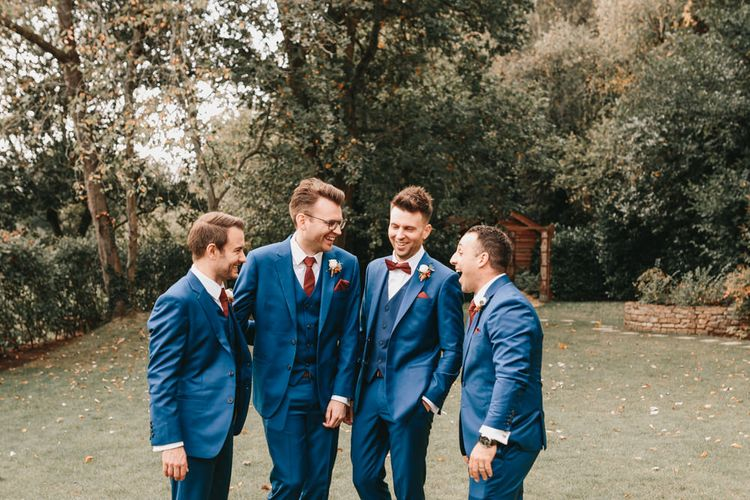 Groomsmen in navy suits laughing together