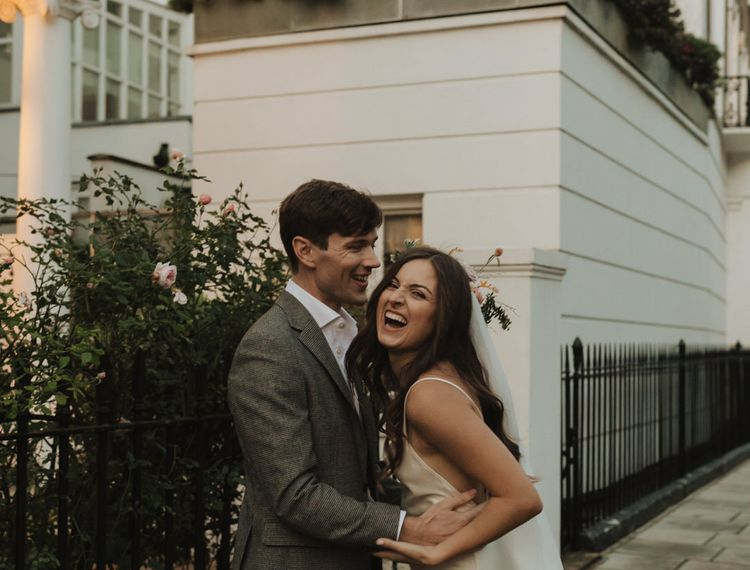 Bride in slip wedding dress laughing during urban couples portraits