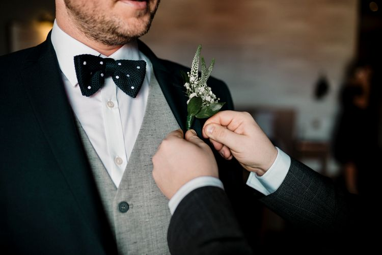Groom putting on a buttonhole on the wedding morning