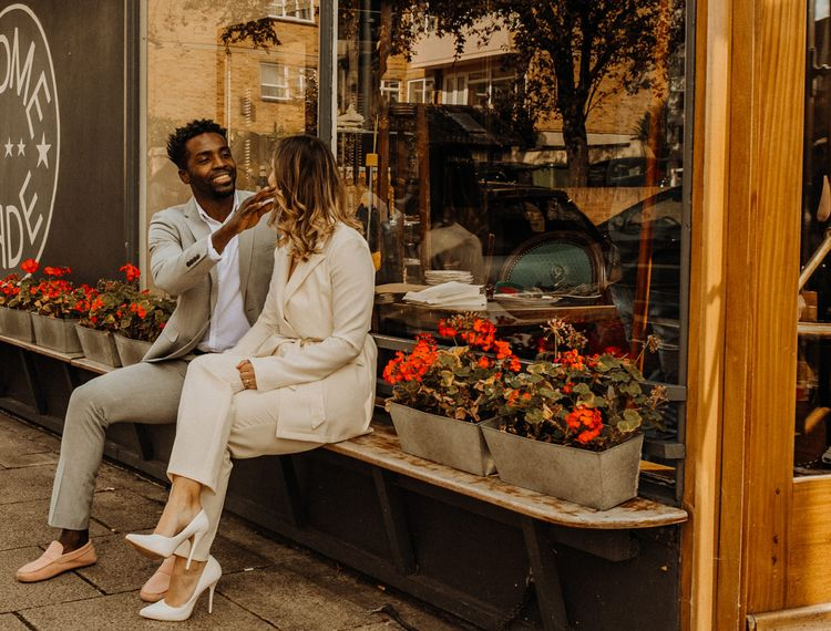 Bride and groom laughing outside their favourite cafe in Portsmouth
