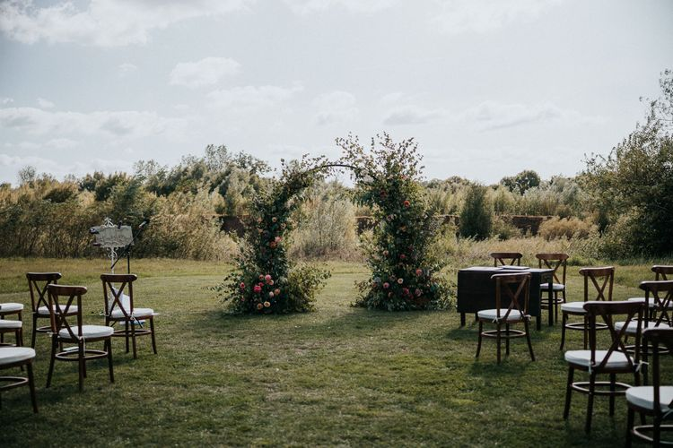 Socially distanced outdoor wedding ceremony at Willow Marsh Farm with floral moon gate altar