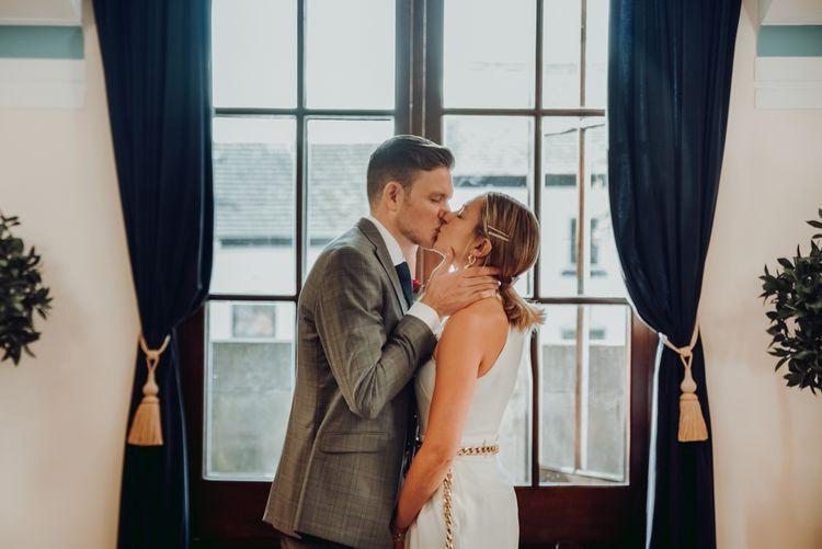 在微型婚礼上,新郎穿着马西莫·杜蒂连衣裤亲吻新娘