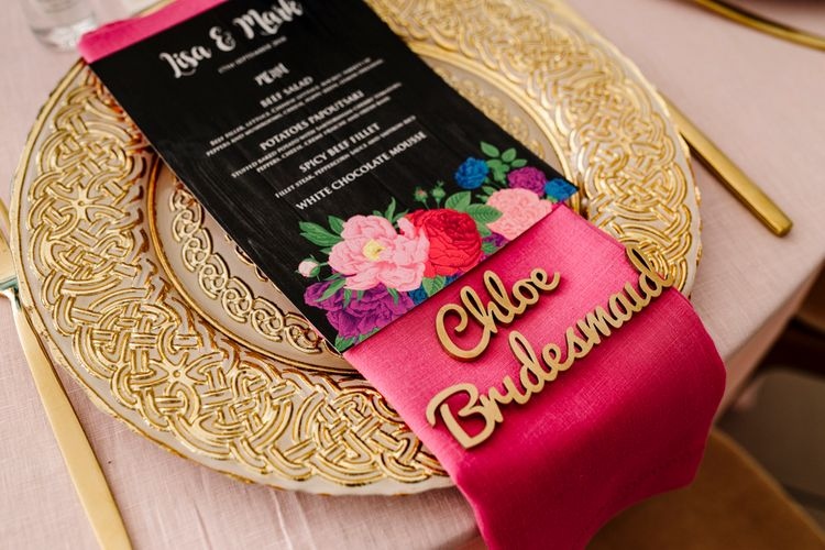 wooden name place settings on pink napkin and gold charger plate