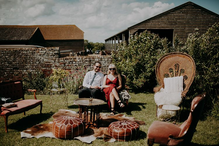 Outdoor seating area with peacock chair, poufs and vintage chairs