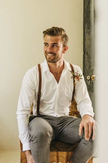 Groom in white shirt and braces for destination wedding