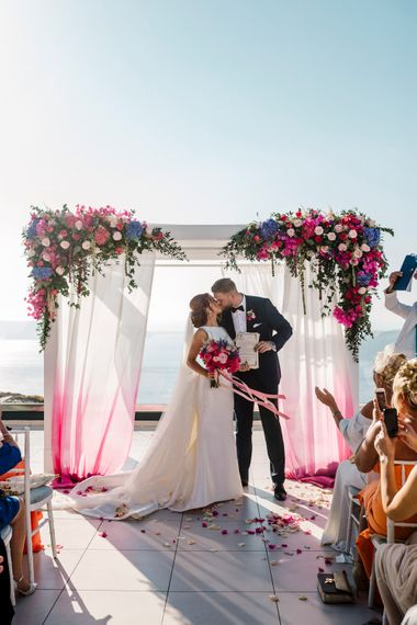 Bride and kissing in front of their floral arch at Santorini wedding