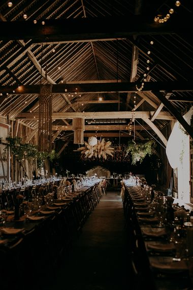 Rustic barn reception with fairy lights, wicker chair and macrame rustic wedding decor