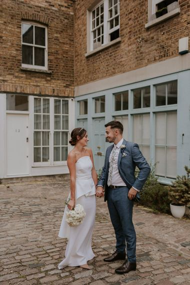 Bride in strapless Roland Mouret wedding dress and groom in blue suit