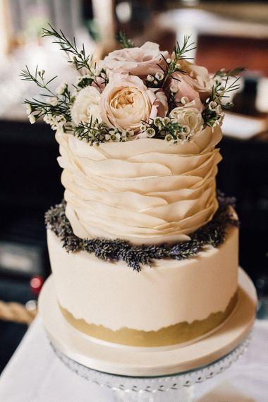 Elegant ruffled wedding cake with floral cake topper