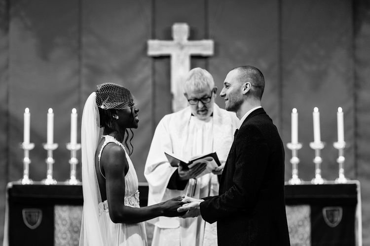 Bride and groom holding hands at the altar of their St Nicholas church wedding in Liverpool