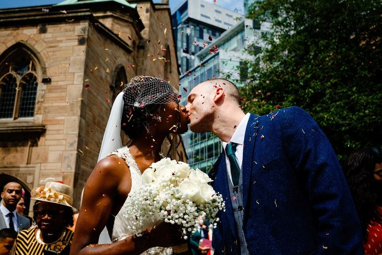 Bride and groom kissing outside St Nicholas Church in Liverpool