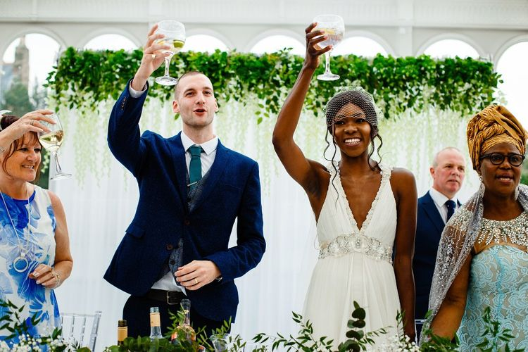 Bride and groom raising their glasses at the glasshouse wedding reception