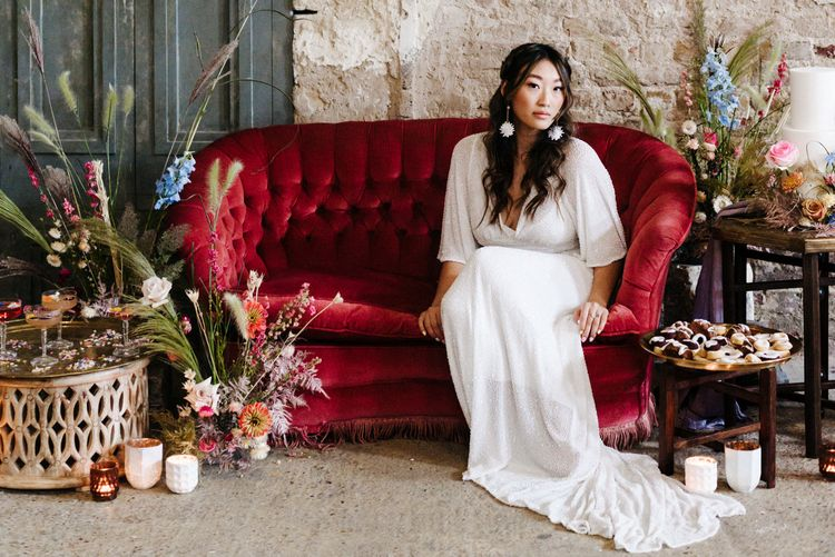 Asian bride in a white sparkly wedding dress sitting on a red velvet sofa