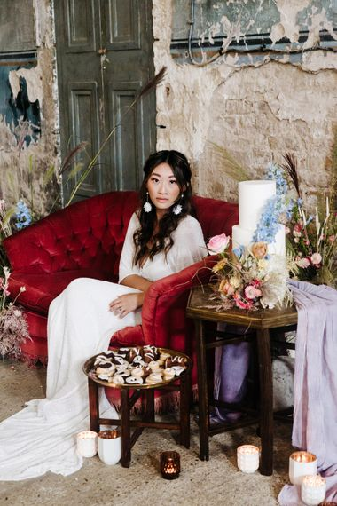 Bride sitting on a red velvet sofa next to a minimal wedding cake decorated with colourful flowers