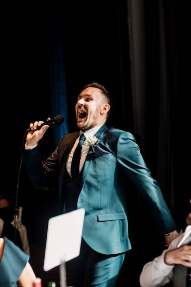 Best man in teal green suit laughing during wedding speeches