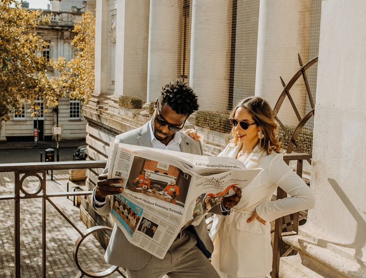 Bride and groom casually reading the newspaper at their intimate elopement