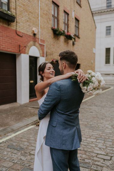 Bride embracing her groom in blue suit