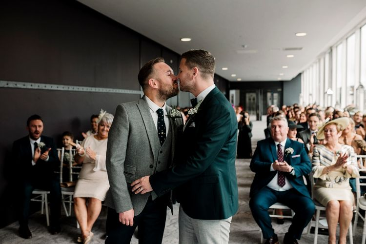 Grooms kissing at Titanic Hotel Liverpool wedding ceremony