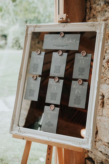 Mirror table plan with ornate frame and wax seals