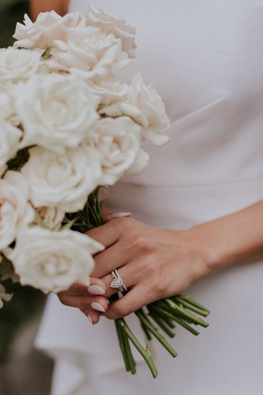 Diamond engagement ring and white rose bouquet