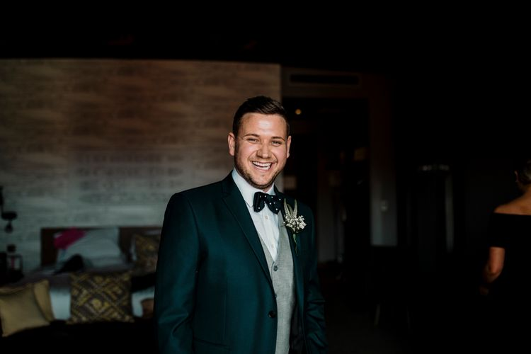 Groom in grey and green wedding suit with bow tie