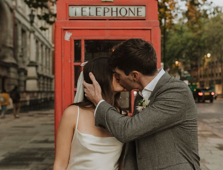 Bride and groom kissing next to a red telephone box