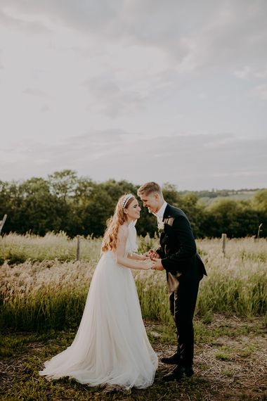 Bride and groom laughing in a field