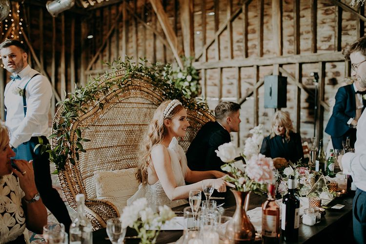 Bride in pearl headdress sitting in a peacock chair
