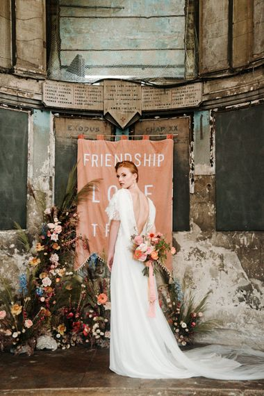 Bride in V back dress holding a colourful bouquet at The Asylum altar
