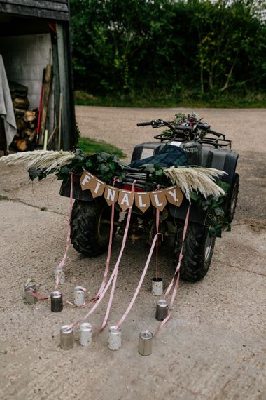 Quad bike with 'finally' bunting and tin can decor