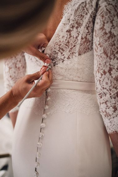 Bride getting ready on the wedding morning into a lace wedding dress