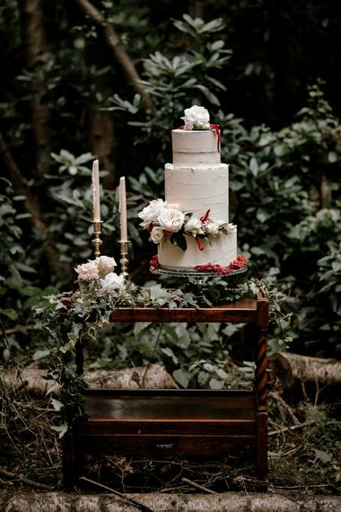 Semi naked wedding cake in vintage dresser at woodland wedding