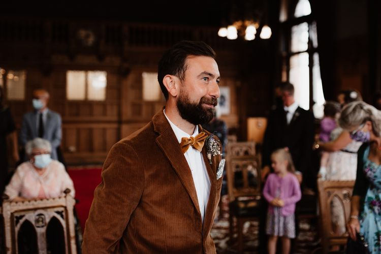 Groom in brown cord jacket and bow tie