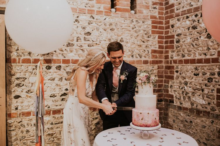 Bride and groom cutting their pink ombre wedding cake