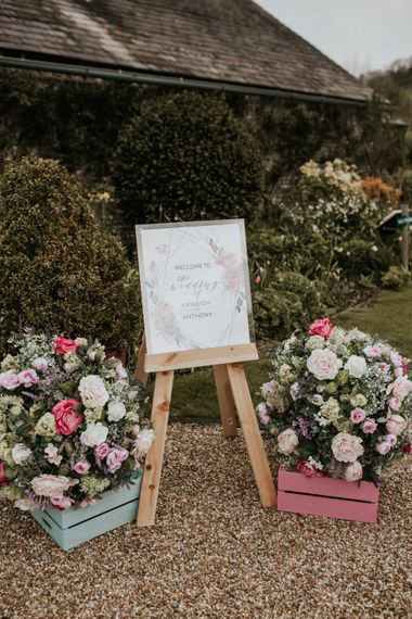 Wedding welcome sign and floral arrangements at Barn wedding