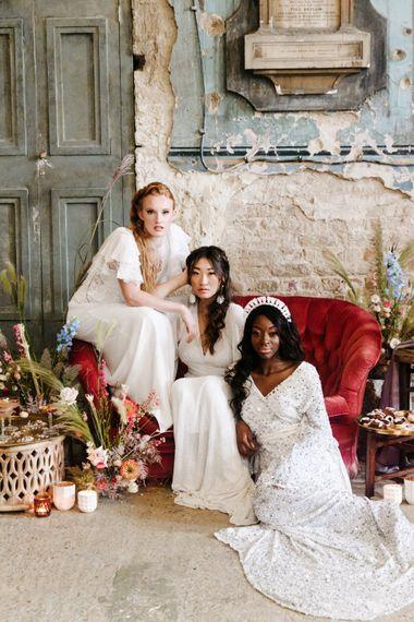 three brides sitting on a red velvet sofa at The Asylum, London