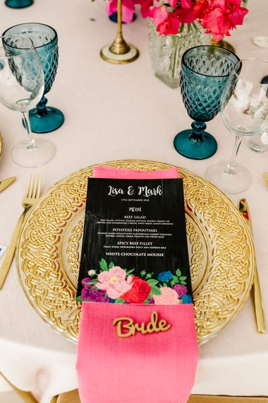 Place setting with gold charger plater, black menu card and pink napkin