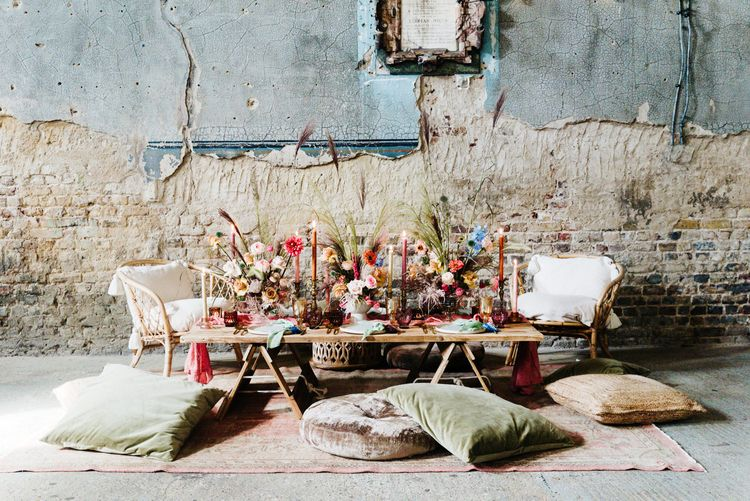 Casual wedding tablescape with rugs, cushions, candles and bright flowers