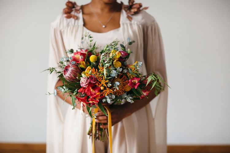 Bright Bouquets with Proteas | Bride in Bespoke Ailsa Monroe Jumpsuit & Cape | Relaxed Industrial Wedding at Ocean Studios, Plymouth | Freckle Photography
