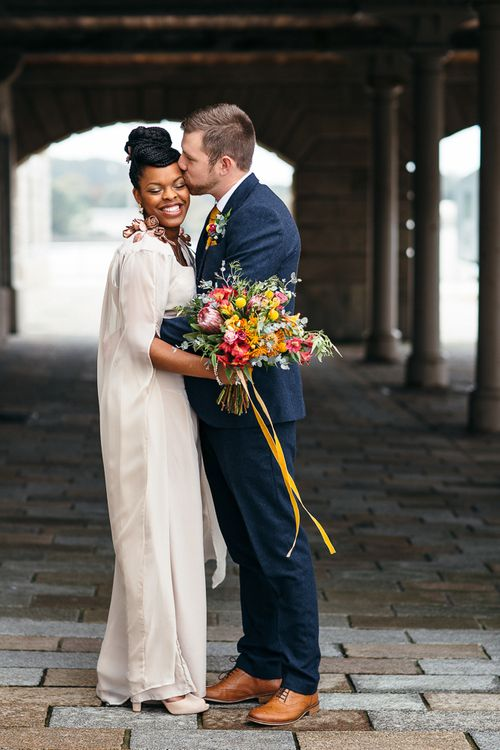 Bride in Bespoke Ailsa Monroe Jumpsuit & Cape | Groom in Next Navy Wool Suit | Relaxed Industrial Wedding at Ocean Studios, Plymouth | Freckle Photography