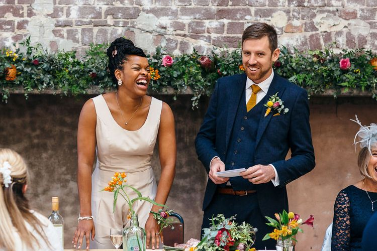 Wedding Speeches | Bride in Bespoke Ailsa Monroe Jumpsuit & Cape | Groom in Next Navy Wool Suit | Relaxed Industrial Wedding at Ocean Studios, Plymouth | Freckle Photography