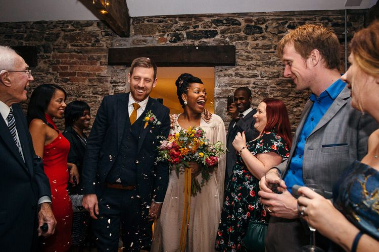 Confetti Exit | Bride in Bespoke Ailsa Monroe Jumpsuit & Cape | Groom in Next Navy Wool Suit | Relaxed Industrial Wedding at Ocean Studios, Plymouth | Freckle Photography